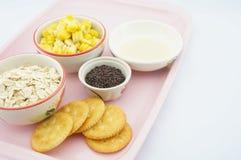 Graan, haver, chocolade, cracker en gezoete condens op roze dienblad Stock Afbeeldingen