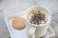 Graangewas op melk in kop en koekje stock afbeelding