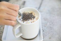 Graangewas op melk in kop met het ontbijt van de vrouwenhand stock foto's
