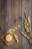 Graangewassenconcept Havermeel in kom dichtbij twijgen van tarwe op de donkere houten ruimte van het achtergrond hoogste meningse Royalty-vrije Stock Foto's