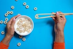 Graangewassenontbijt met melk en eetstokjes voor sushi op blauwe achtergrond stock foto's
