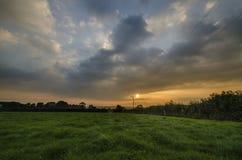 Graanstelen op landbouwbedrijfgebieden met mooie zonsonderganghemel, Cornwall, het UK stock foto