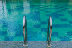 Grab bars in the blue swimming pool Royalty Free Stock Images