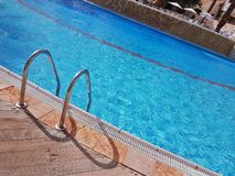 Grab bars ladder in the blue luxury swimming pool. Royalty Free Stock Photography