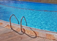 Grab bars ladder in the blue luxury swimming pool. Royalty Free Stock Image
