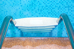 Grab bars ladder in the blue swimming pool. Stock Photography