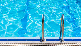 Grab bars ladder in the blue swimming pool Stock Image