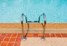 Grab bars ladder in the blue swimming pool Royalty Free Stock Photos