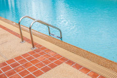 Grab bars ladder in the blue swimming pool Stock Images
