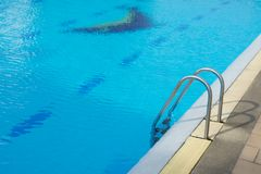 Grab bars ladder in the blue swimming pool. Concept Healthy exer Royalty Free Stock Image