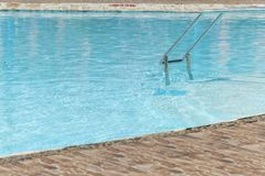Grab bars ladder in the blue swimming pool. Curved side of a swimming pool with stairs.  royalty free stock photography