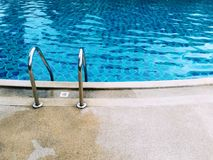 Grab bars ladder in the blue swimming pool. Royalty Free Stock Photos
