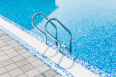 Grab bars ladder in the blue swimming pool. Summer. Stock Photos