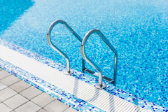 Grab bars ladder in the blue swimming pool. Summer. Royalty Free Stock Photo