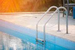 Grab bars ladder in the blue swimming pool with Orange sun light Royalty Free Stock Photo