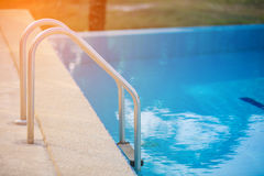 Grab bars ladder in the blue swimming pool with Orange sun light Stock Photos
