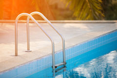 Grab bars ladder in the blue swimming pool with Orange sun light Royalty Free Stock Photos
