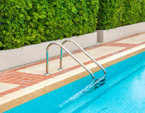 Grab bars ladder in the blue swimming pool Royalty Free Stock Image