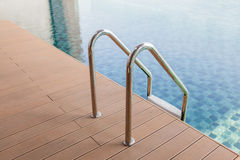 Grab bars ladder entrance to clear blue swimming pool. Stock Photos