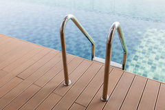 Grab bars ladder entrance to clear blue swimming pool. Royalty Free Stock Photography