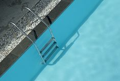 Grab bars ladder in swimming pool Stock Image