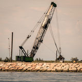 Grab crane in action for building a seawall. Royalty Free Stock Image