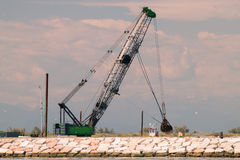 Grab crane in action for building a seawall. Royalty Free Stock Photos