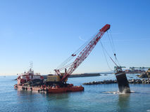 Grab Dredge with Clamshell Bucket unloading gravel to replenish Stock Photo