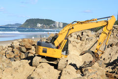Grab excavator. Boulder wall construction. Grab excavator. Boulder wall construction after severe erosion of the beach. Miami beach, QLD, Australia Stock Photography