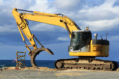 Grab excavator. Boulder wall construction. Grab excavator. Boulder wall construction after severe erosion of the beach. Miami beach, QLD, Australia Royalty Free Stock Photo
