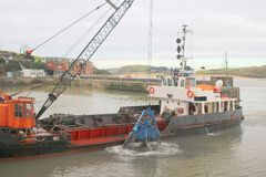 Grab hopper dredger at work. A grab hopper dredger at work in Padstow harbour in Cornwall, England Stock Photos