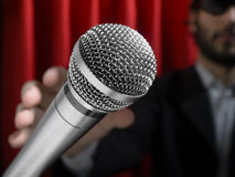 Grab the mic. A youg man on stage about to grab a microphone stock photos