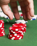 Grab Poker Chips. A close up as a hand moves in to grab some red poker chips on a poker table Royalty Free Stock Image