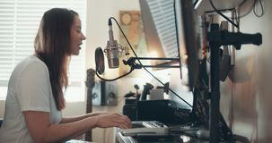 Grabación de la mujer joven una pista en su estudio casero metrajes