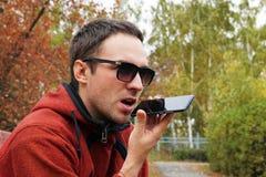 Grabación en el dictáfono ocio, tecnología, comunicación y concepto de la gente - hombre del inconformista usando el registrador  imagenes de archivo