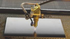 Grabando en un primer plateado de metal, el proceso de calificar el tipo del logotipo con un laser almacen de metraje de vídeo