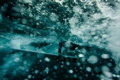 Grabb i den svarta baddräkten som flödar ner att rymma en dyk för bränningbräde under vågen arkivfoto