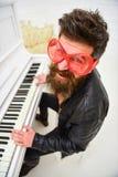 Grabb i jätte- röd solglasögon, medan spela pianot Man gladlynt spela för pianist Komiskt aktörbegrepp Man i läder Arkivbild