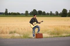 Grabb i läderomslaget som spelar den akustiska gitarren på sida av vägen Royaltyfria Foton