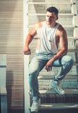 Grabb i moderiktigt ärmlös tröja- och jeansmode Den unga mannen sitter på stege Idrotts- macho med den muskulösa bröstkorgen och  royaltyfri fotografi