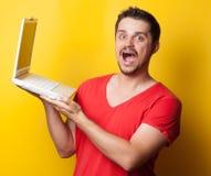 Grabb i t-skjorta med bärbar datordatoren arkivfoto