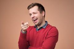 Grabb med borstet som ler och uttrycker positiva sinnesrörelser, medan peka på kameran royaltyfri bild
