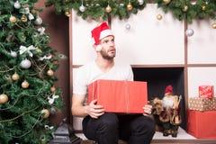 Grabb med den allvarliga framsidan i ask för gåva för santa hatthåll Royaltyfri Foto