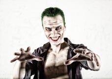 Grabb med den galna jokerframsidan, grönt hår och idiotisk smike carnaval dräkt Royaltyfria Bilder