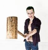 Grabb med den galna jokerframsidan, grönt hår och idiotiskt leende carnaval dräkt hållande hammare för syrsa Royaltyfri Bild