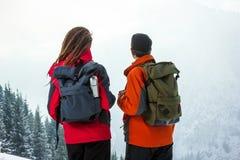 Grabb med en flicka i bergen på bakgrunden av ett vinterlandskap royaltyfria foton