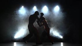 Grabb med en flicka i hjälmar och boxninghandskar som slår i cirkeln i mörkret silhouette Ljus bakifrån rök arkivfilmer