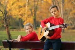Grabb med en flicka i parkera med en gitarr Royaltyfri Foto