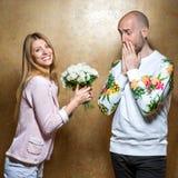 Grabb med en flicka på dagen för valentin` som s ger blommor Arkivfoton