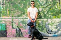 Grabb med en hund labrador på spela för gata arkivfoton